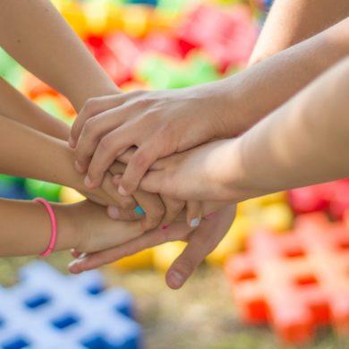 Kinderhände übereinander vereint.